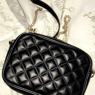 svart liten väska med guld kedja
