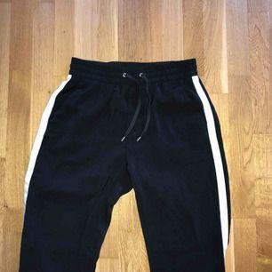 Svarta tracksuit-liknande byxor med vit rand på sidan. Frakt ingår inte:)
