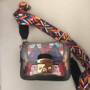 Svart väska med färgglada detaljer samt ett brett band. Sparsamt använd. Kan fraktas