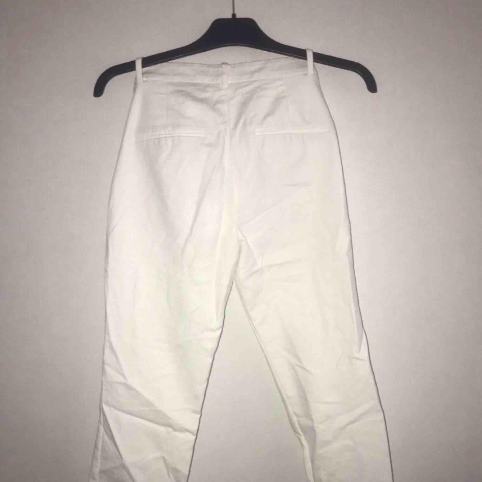 Vita kostym byxor med slits längst ner vid sidorna av benen. Jeans & Byxor.