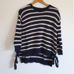 Mysig stickad tröja med tre kvarts långa ärmar i marinblå färg med vita ränder. Band i sidorna som knyts. Ser kanske lite hängig ut på galgen men sitter fint på! Storlek S.