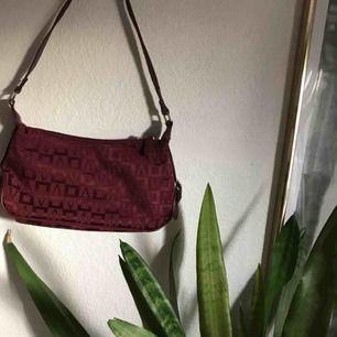 Sååå snygg vinröd liten handväska med logo-tryck! 😍 Perfekta 90s/00-väskan! Skinndetaljer på sidorna i fuskskinn och perfekt vinröd färg. 80kr+frakt