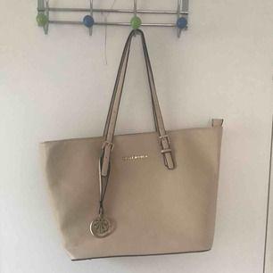 En beige handväska från bellewomen. Saknar svart detaljräm på ena handtaget. Väldigt rymlig. Kan mötas upp i Sthlm, annars ingår inte frakt i priset