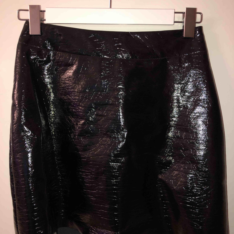 Svart lack-kjol från monki Aldrig använd. Möts i Stockholm, köparen står annars för frakt. Kjolar.
