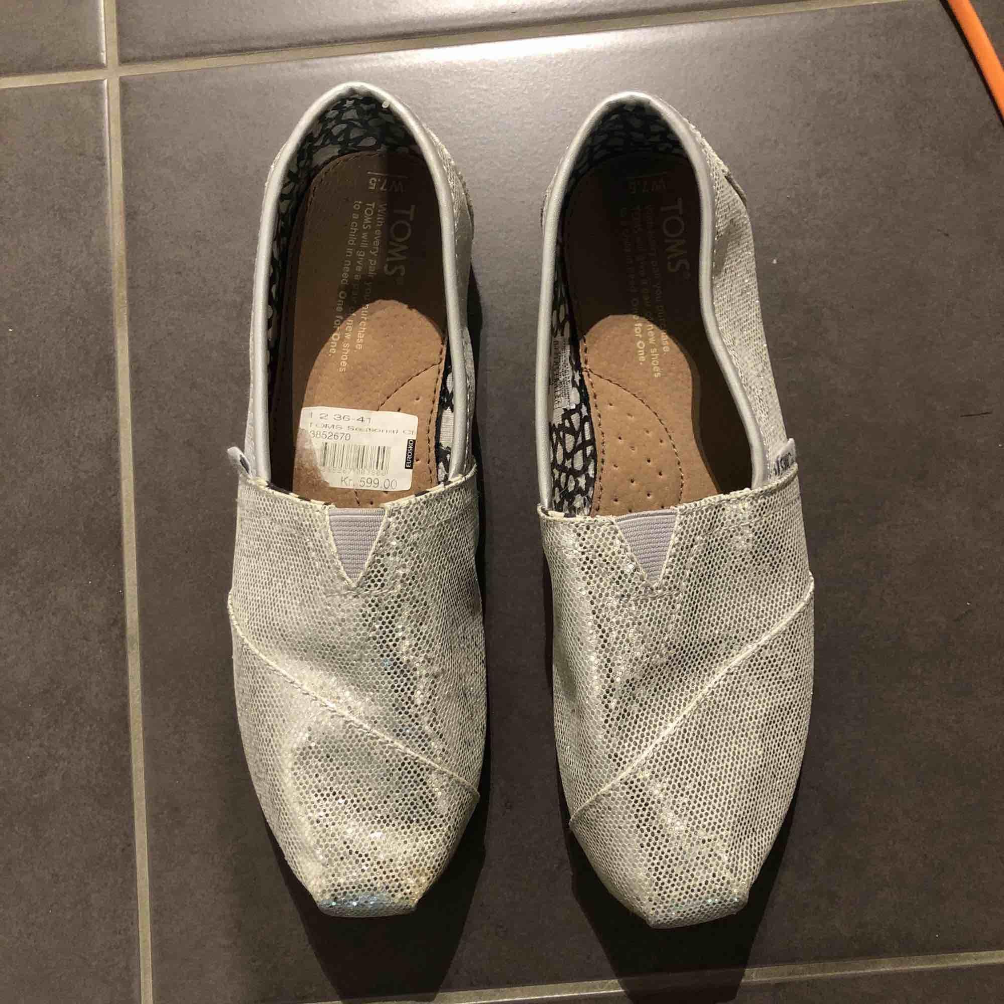 Storlek 38. Glitter silver TOMS. Använda 1-2 ggr. Nypris 599. Jättefint skick. Kan mötas upp i Stockholmsområdet.. Skor.