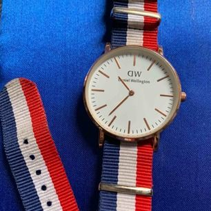 Gammal Daniel Wellington klocka ! Guld med blå-vit-röd band Använd men fortfarande fin. Klockan har stannat men kan fortfarande användas mer som accessoar. Nypris 1499. Pris kan diskuteras.