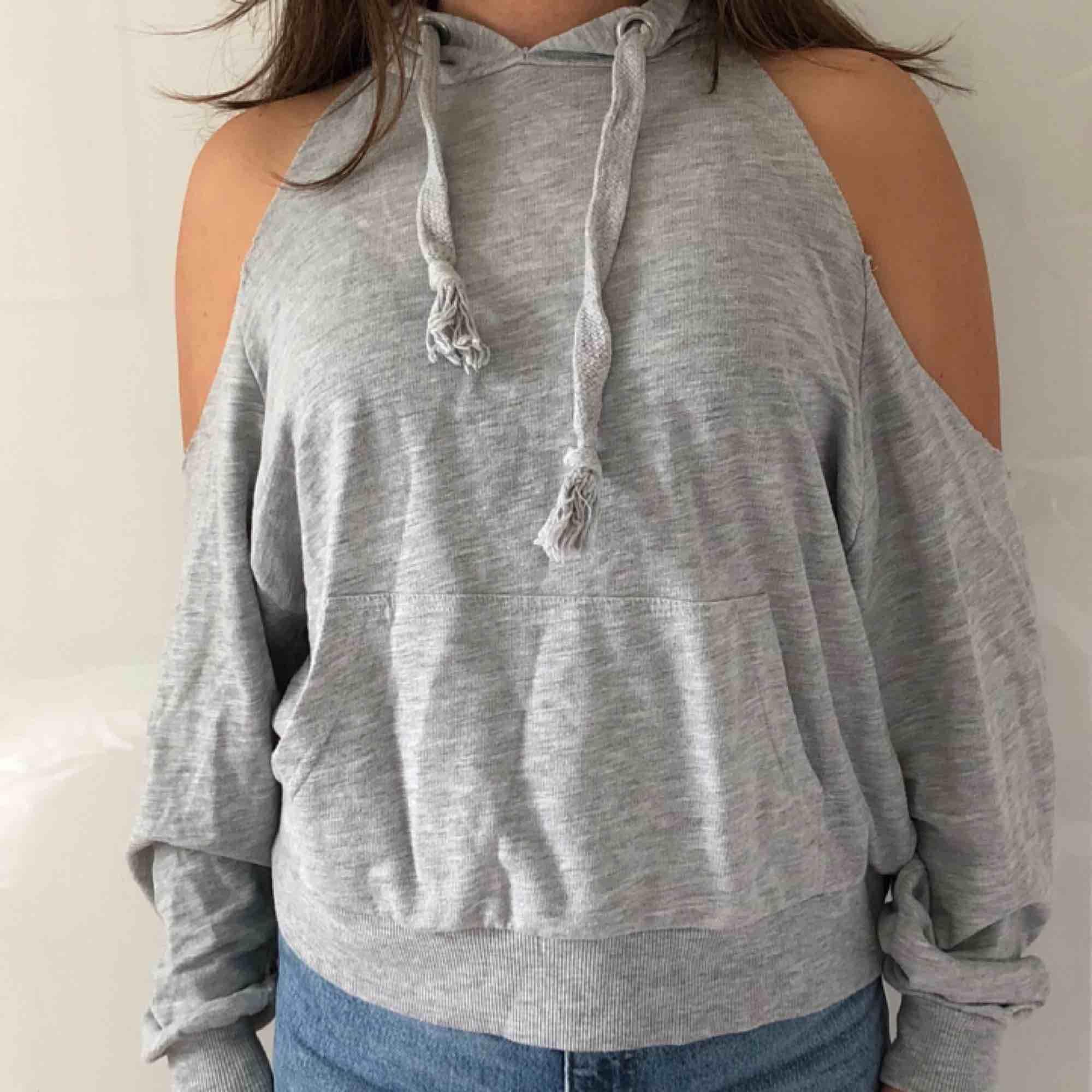 Oversized grå hoddie med luva, ficka och cut-outs på axlarna. Från Bershka! Frakt tillkommer.. Huvtröjor & Träningströjor.