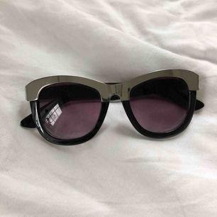 Solglasögon från Glitter. Stora svarta med silver ram.