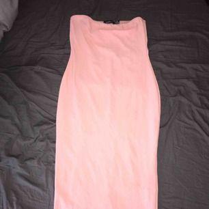 En rosa klänning utan band med stretchigt material. Den stannar också bra där den är även fast den inte har band.