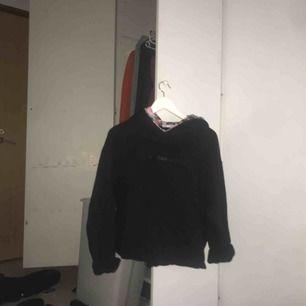 En svart hoodie med blommig insida på luvan
