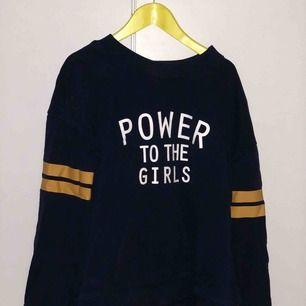 """""""Power to the girls"""" tjocktröja. Mörkblå med gula remsor på ärmarna. Säljer pga att jag inte använder den längre."""