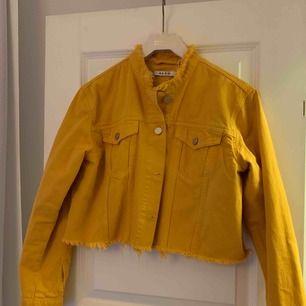Helt ny croppad jeansjacka från NAKD. Jättefin gul färg och slitning. Endast provad inomhus. Köparen står för ev frakt 63kr med postnord.