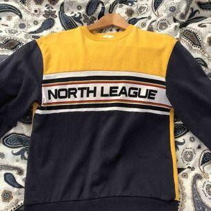 Gul & mörkblå sweatshirt, har en fettfläck på magen men den syns knappt! Frakt tillkommer