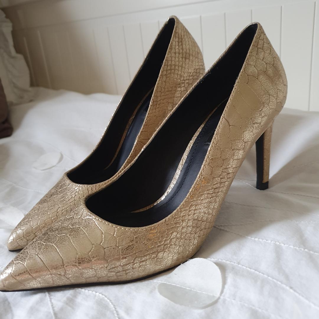 Guldiga klackar från Zara i ormskinns imitation.  Köparen står för frakt betalning via swish. Skor.