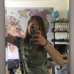 Vanlig T-shirt med camoflauge-print i olika gröna nyanser. Använd 2 gånger men är i fint skick! FRAKT INGÅR I PRISET. Skulle även vara fin att croppa :).