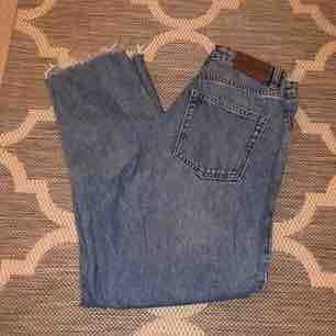 Supersnygga vintage/mom jeans från Monki i modellen Kimomo! De är högmidjade och sitter snyggt & tajt över rumpan/låren men lösare vid smalbenen! Råa kanter/raw edges. Markerade som strl 26 men passar 27 också . Jeans & Byxor.