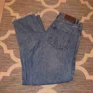 Supersnygga vintage/mom jeans från Monki i modellen Kimomo! De är högmidjade och sitter snyggt & tajt över rumpan/låren men lösare vid smalbenen! Råa kanter/raw edges. Markerade som strl 26 men passar 27 också