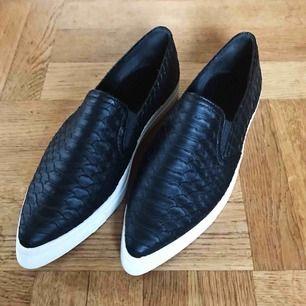 Spetsiga, svarta, fejk-ormskinns skor från NA-KD.  Aldrig använda utomhus! Bara provade!  Köpta på REA, därav priset! Säljer pga. att dem är för små för mig.