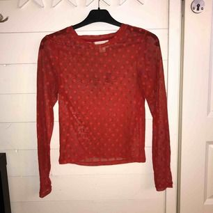 en röd mesh tröja med prickar som detalj, sitter inte slimmat eller tajt.
