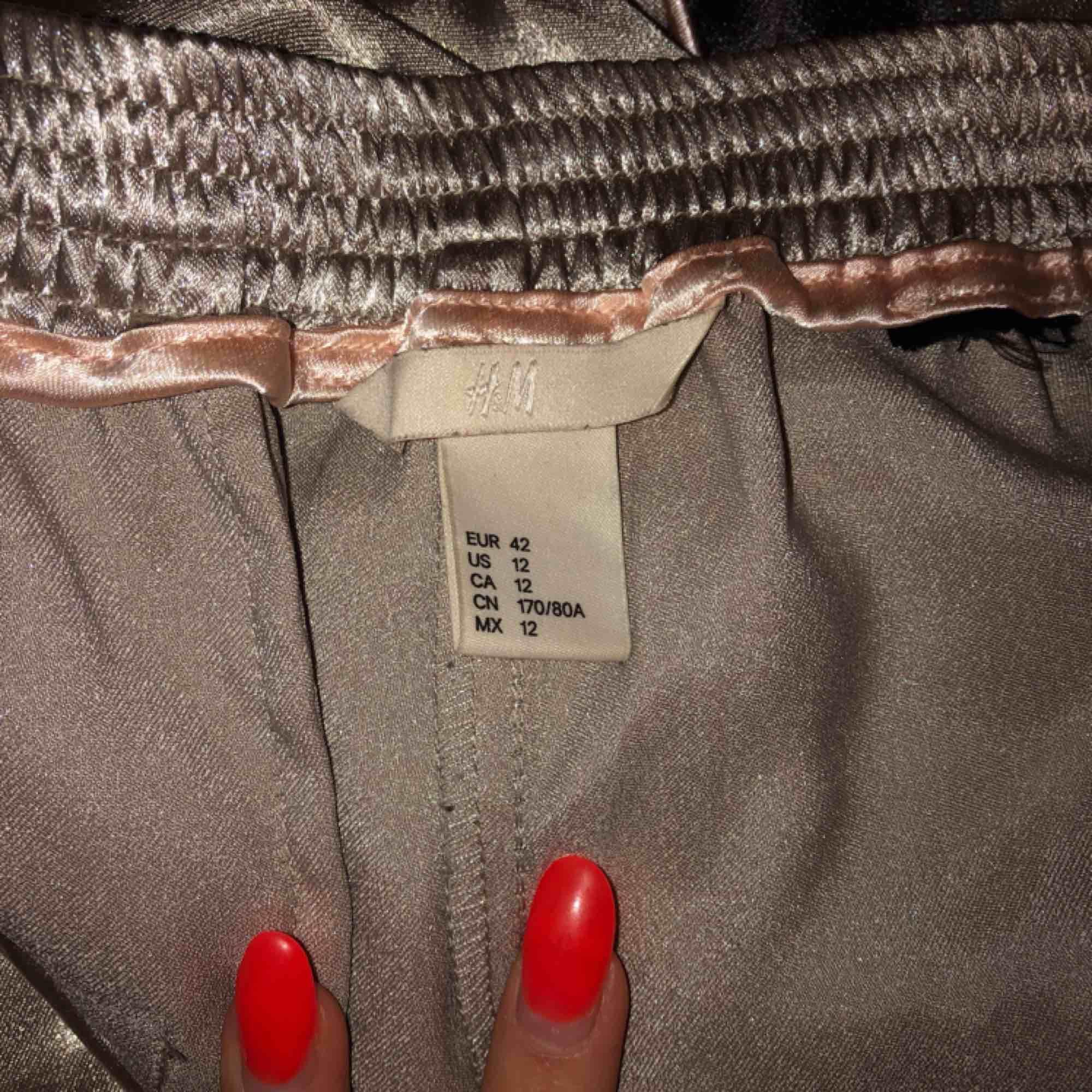Super fina part byxor med slitsar av dragkedjor och med en fantastisk guldfärg som skiftar i olika ljus. Jeans & Byxor.