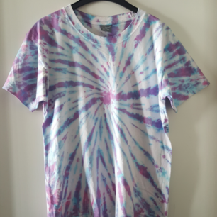 Vintage t-shirt med batik. Storlek XL, men skulle nog mer säga den är ca som en L. Har ett pyttelitet igensytt hål nedtill bak på t-shirten (se bild 2). Kan skickas om köparen står för fraktkostnaden som blir 36kr.