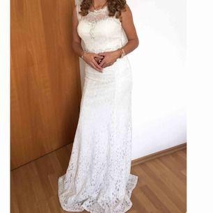 En vacker vit, glittrig spets klänning med jätte fina glittriga detaljer. Den verkligen glittrar i solen. Ger form till kroppen och är bekväm. Använd endast en gång. Passar såväl som balklänning, festklänning som bröllopsklänning.  Pris kan diskuteras.
