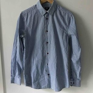 Blåvit-randig skjorta, har en mindre reva vid en knapp