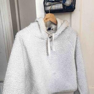 Super mysig vit fluffig hoodie, ganska croppad med vida armar, ser ganska fläckig och missfärgad ut på bilderna men detta är kamerans fel
