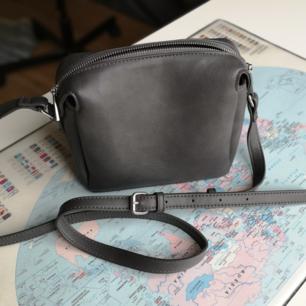 Skitsnygg handväska i skinnimitation från Åhléns. I princip ny. Jättefin kvalitet och snygg grå färg. Skicka pm om du vill ha mått. Justerbart axelband.
