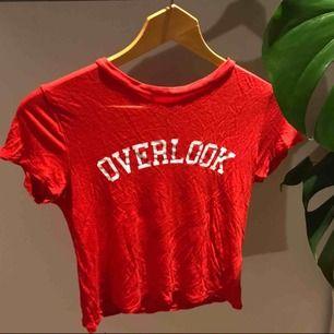 """Jättefin klarröd t-shirt från H&M aldrig använd då den inte kommit till användning. Med tryckt text """"overlook"""" Bra till sommaren och varmare väder! Frakt tillkommer :)"""