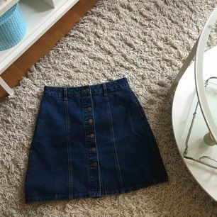 Jeans-kjol i mörk tvätt, okänt märke. Står 34 inuti men har mätt med en kjol i strl 36 och denna är ett par mm större till och med. Så skulle säga att den passar en 36/38. Använd en gång!