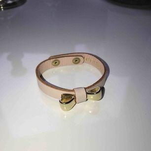 Läderarmband med en guldig rosett, äkta läder, ej äkta guld. Frakt tillkommer (18kr)