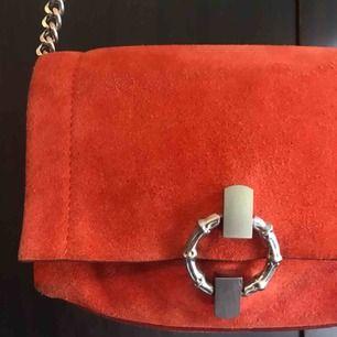 Väska från Zara i orange med kedja. Lite slitningar på baksidan som inte syns när den används