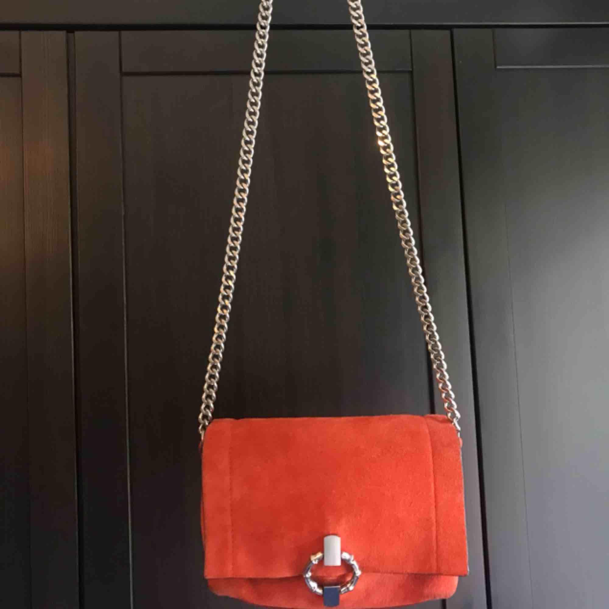 Väska från Zara i orange med kedja. Lite slitningar på baksidan som inte syns när den används. Väskor.