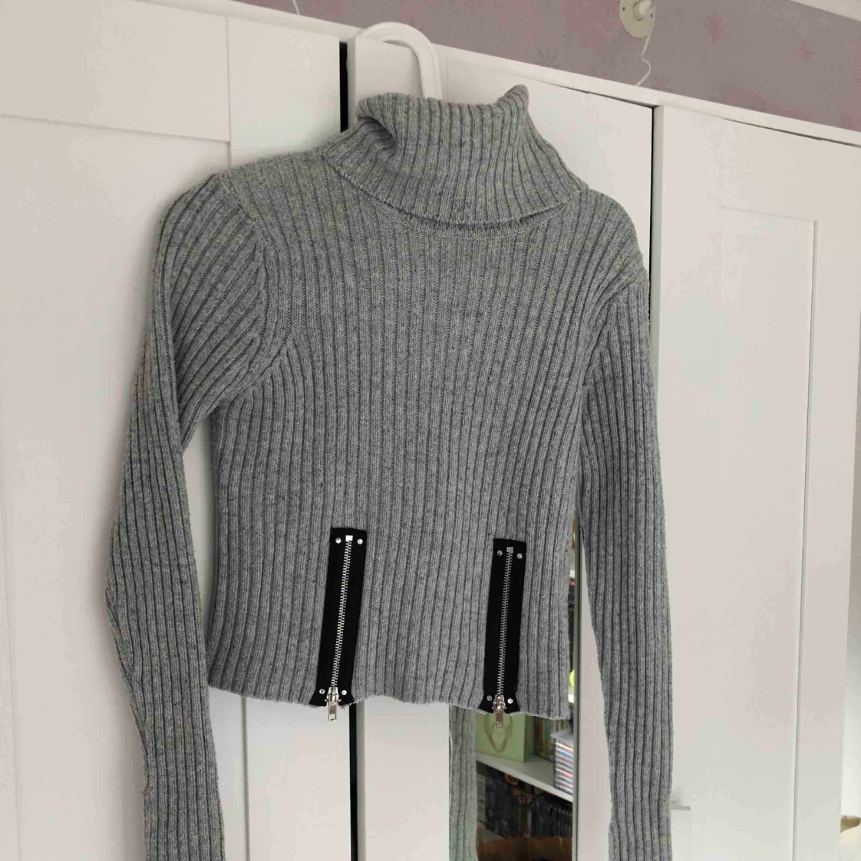 Grå stickad tröja med dragkedjedetaljer, knappt använd. Köparen står för frakten!. Tröjor & Koftor.