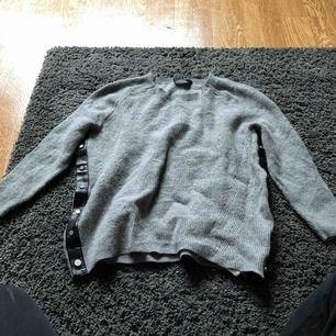 Grå stickad tröja från Disel med knappar i sidan. (Knapparna går att öppna och stänga om man vill). Aldrig använd