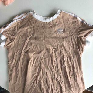 Adidas T-shirt köpt från JD, lite beige/gammelrosa Kostar egentligen 300kr Kan inte frakta utan får mötas runt om i jkpg