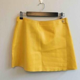 Kort gul kjol i skinn i storlek small. Midjemått 76 CM  och länge 37 CM. Köpare betalar frakt på 50kr, Meet up i Stockholm funkar också bra.