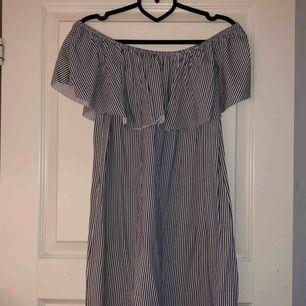 Fin off shoulder-klänning med volang både fram o bak över brösten och ryggen. Köparen står för fraktkostnad.
