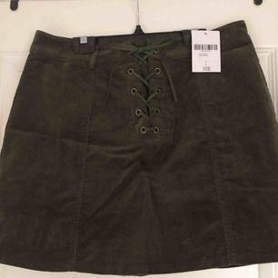 Oanvänd kjol med snörning framtill. Prislapp finns kvar. Köparen står för fraktkostnad.