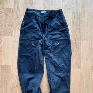 Svarta cargobyxor med fickor och dragsko, storlek 38, mycket fint skick. Köparen står för frakt, 60kr, har swish 🦋