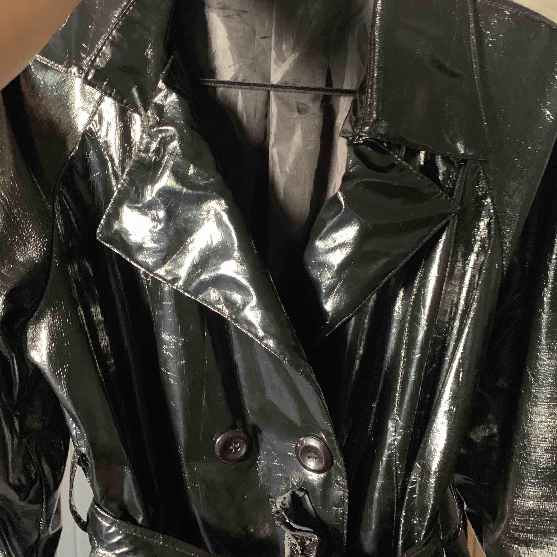 Tunn lack jacka i svart köpt i second hand. Bältet är lite trasigt.   Frakt tillkommer . Jackor.