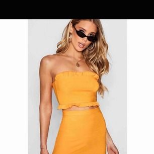 Tvådelat set med bandeau-top och kjol i en snygg orange/gul färg. Storlek 36. Aldrig använd endast testad. Köparen står för frakt.