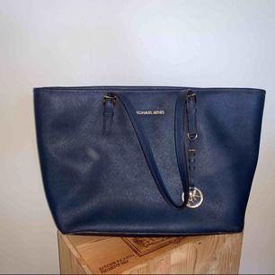 Denna Michael Kors handväska är i modellen Jet Set medium tote och färgen marinblå. Väskan är i princip helt utan slitage och generellt i ett mycket gott skick. Inköpspriset var 2700 kr. Väskan är självklart äkta och köpt från NK i Stockholm.