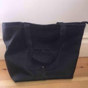 Jättefin svart väska med två glitterränder (se bild) med både innefack och ytterfack. Använd fåtal gånger