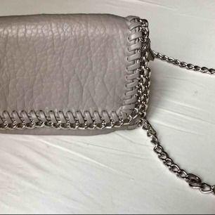 Snygg liten väska i grått skin, köpt på scorett! Ordinariepris: ca 500kr. Väskan hänger på axeln med en silverkedja.  Betalning: Swish