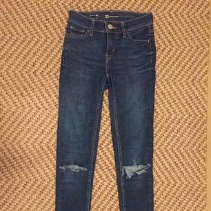 Ett par fina jeans från Levis. I modellen super skinny och storlek 23. Fin mörkblå färg och hål på knäna. Originalpris 500kr men säljs för 150kr. Säljs eftersom dem inte passar längre.  Vi delar på tillkommande fraktkostnaden.