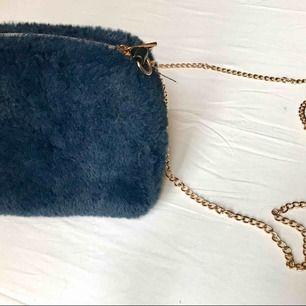 Snygg liten väska i blå päls! Väskan hänger på axeln med en smal guldkedja.   Betalning: Swish