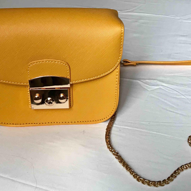 Snygg gul skinnväska! Väskan hänger på axeln med en smal guldkedja och en rem av gult skinn. Betalning: Swish. Väskor.