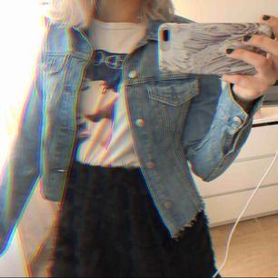 Croppad jeansjacka från H&M. Inga slitningar eller fläckar mm. Bra skick! Jättesöt till våren och sommaren.